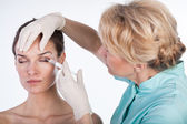 Doctor injecting botox in the forehead — Stock Photo