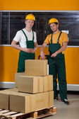 Men with fork pallet truck full of boxes — Stock Photo