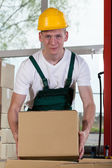 Portrait of a warehouse worker lifting a box — ストック写真