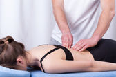 Physiotherapist touching muscle of the back — Foto Stock