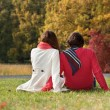 Couple sitting on the ground in the park — Stock Photo #53125445