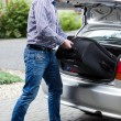 Man putting luggage into car trunk — Stock Photo #53498407
