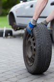 Rolling a spare of wheel — Stock Photo