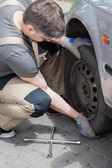 Mechanic changing wheel in car — Foto de Stock