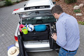 Dad preparing car trunk for holiday — Stock Photo
