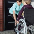 Caregiver helping disabled woman entering home — Stock Photo #53556061