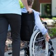 Nurse walking with elderly woman on wheelchair — Stock Photo #53556319