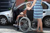 女の子の車になって車椅子で女性を助ける — ストック写真