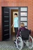 Caregiver inviting woman on wheelchair to nursing home — Stock Photo