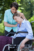 Nurse comforting an old woman on wheelchair — Stock Photo