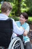 Senior woman on wheelchair with her caregiver — Stock Photo