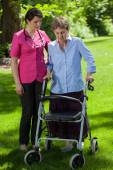 Nurse walking beside woman with orthopedic walker — Stock Photo