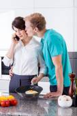 Husband kissing his wife during breakfast preparation — Stock Photo