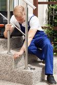 Man repairing a stair railing — Stock Photo