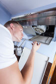 Handyman repairing kitchen extractor fan — Stock Photo