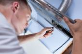 Repairman mending a kitchen extractor — Stock Photo