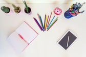 Open exercise book, pencil crayons and tablet on white desk — Stock Photo