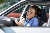 Woman doing makeup in car — Stock Photo