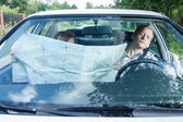 Woman with a map in car — Stock Photo