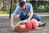 Man lying girl in recovery position — Stock Photo
