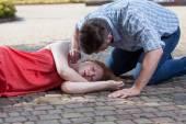 Man checking pulse of fainted girl — Stock Photo