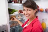 Woman taking doughnut from fridge — Foto de Stock