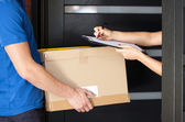 Woman signing parcel delivery papers — Stock Photo