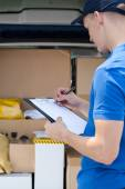 Delivery guy filling in documents — Stock Photo