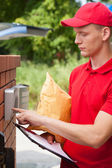 Delivery guy calling on entryphone — Stock Photo
