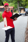Delivery guy giving a packet — Stock Photo