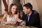 Smiling couple waiting for dinner in restaurant — Stock Photo