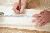Hands measuring wooden plank with measuring tape and pencil — Stock Photo