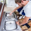 Young man repairing kitchen sink — Stock Photo #55534469