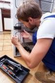 Man repairing fridge at home — Stock Photo