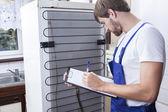 Handyman under kylskåp reparation — Stockfoto