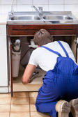 Handyman fixing sink in the kitchen — Stock Photo
