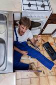 Mad man during rapair in kitchen — Stock Photo