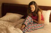 Woman in bed having abdominal cramps — Stok fotoğraf
