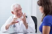 Doctor prescribing patient red pills — Stock Photo