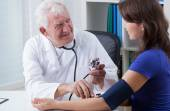 General practitioner taking blood pressure — Stock Photo