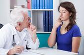 Physician diagnosing patient — Stockfoto