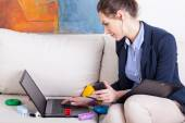 Young mother using laptop to work at home — Stock Photo