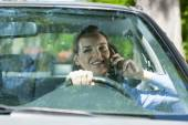 Woman calling mobile phone during driving a car — Stock Photo