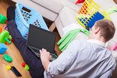 Man using laptop sitting on the floor — Stock Photo