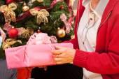 Grandpa putting present under Christmas tree — Stock Photo