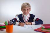 Smiling child writing at school — Stock Photo