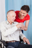 Nurse giving disabled man glass of water — Stock Photo