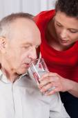 Nurse helping disabled with drinking water — Stock Photo