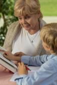 Granny and grandchild reading book — Stock Photo
