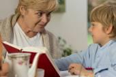 Senior babysitter caring about schoolboy — Stock Photo